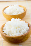 White rice. Cooked white rice served in antique wood bowls on a bamboo placemat Stock Photography