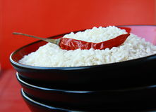 White rice in a black bowl with chili pepper Stock Image