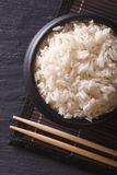 White rice in a black bowl and chopsticks. vertical top view Stock Photos
