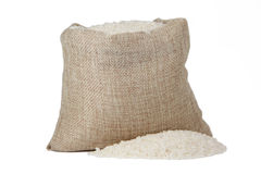 White rice in burlap sack isolated on white background Stock Photos