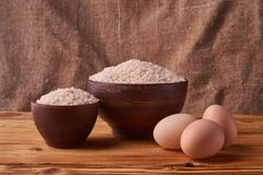 White rice in clay bowl on table and eggs on wood background. Concept asian food. White rice in clay bowl on table and eggs on wood background royalty free stock photography
