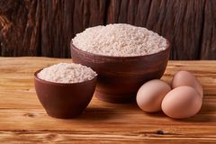 White rice in clay bowl on table and eggs on wood background. Concept asian food. White rice in clay bowl on table and eggs on wood background royalty free stock photos