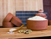 White rice in a clay bowl and in a wooden spoon. Bay leaves and Stock Images