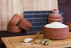 White rice in a clay bowl and in a wooden spoon. Bay leaves and Royalty Free Stock Images