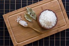 White rice in a clay bowl and in a wooden spoon. Bay leaves and royalty free stock photography