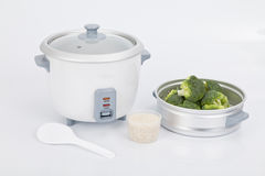 White rice cooker with accessory to cook steamed vegetables Stock Images