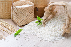 White rice grains in burlap bag and basket on wooden background Stock Photos