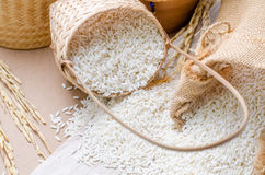 White rice grains in burlap bag and basket on wooden background Stock Photography