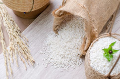 White rice grains in burlap bag and basket on wooden background Royalty Free Stock Photography