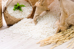 White rice grains in burlap bag and basket on wooden background Stock Image