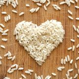 White rice grains in heart shape on wooden cutting board, in square format for social media, banners, and backgrounds. royalty free stock photo