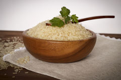 White rice with herbs. Uncooked rice with herbs in a wooden plate on linen napkin Royalty Free Stock Photos