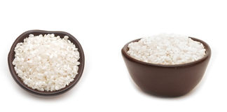 White rice in round brown cup. On white background Stock Images