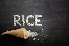 White rice scattered over the dark wooden table of a paper bag. Royalty Free Stock Photography