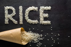 White rice scattered over the dark wooden table of a paper bag. Royalty Free Stock Image
