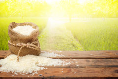 White rice in small burlap sack on wooden table Royalty Free Stock Photo