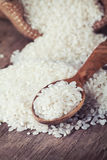 White rice spill out of the bag and wooden spoon on the table Stock Images
