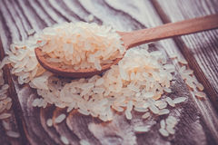 White rice in spoon on wooden background Stock Photography