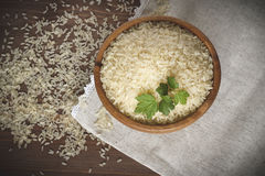 White rice. Uncooked rice with herbs in a wooden plate on linen napkin Stock Images