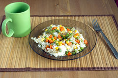 White rice with vegetables on plate over wicker mat Stock Photo