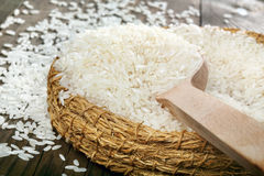 White rice in wicker bowl with wooden spoon on wooden table Stock Photography