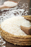 White rice in wicker bowl with wooden spoon on wooden table Stock Image