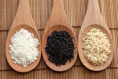 White rice and wild rice and brown rice in a wooden spoons. White rice and wild rice in a wooden spoons on bamboo napkin. Close-up Royalty Free Stock Photography
