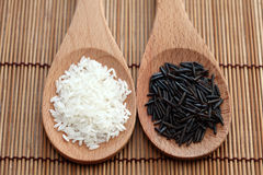 White rice and wild rice in a wooden spoons. On bamboo napkin. Close-up Royalty Free Stock Image