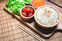 A white rice in wooden bowl and chopsticks with carrots, black sesame , and tomatoes vegetables on wooden board. Healthy food and Royalty Free Stock Photography