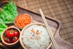 A white rice in wooden bowl and chopsticks with carrots, black sesame , and tomatoes vegetables on wooden board. Royalty Free Stock Images