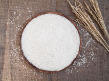 White rice on the wooden plate and rice plant , uncooked raw cer Stock Photos