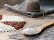 White rice in a wooden spoon. On the sackcloth with ball of twine on an old wooden table Royalty Free Stock Image