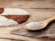 White rice in a wooden spoon. On the sackcloth on an old wooden table Royalty Free Stock Photo