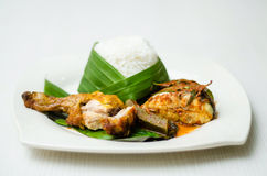 White Rice. A wrapped white rice in plate on a dining table served with fried chicken and a portion of fish royalty free stock photos