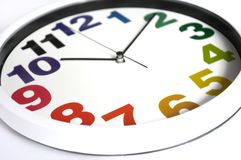 A white rim clock with colored numbers Royalty Free Stock Images