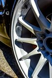 White rims on a black car with red breaks peeking out from the s Royalty Free Stock Images