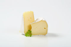White rind cheese. Two slices of white rind cheese with parsley on white background royalty free stock image