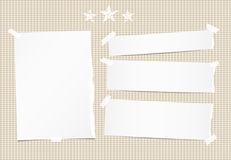 White ripped note, notebook, copybook paper sheet, strips and stars on brown squared background. Royalty Free Stock Photo