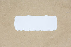 White ripped piece of paper on brown document texture paper Royalty Free Stock Photography
