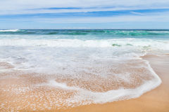 White Ripples of Surf Wave against Golden Sand with Sky stock photo