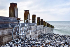 White Road Bike Beside the Brown Wooden Gate Besode the Sea Royalty Free Stock Image