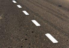 White road line on dirty asphalt texture. Royalty Free Stock Photos