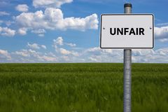 White road sign. the word UNFAIR is displayed. The sign stands on a field with blue background stock photo