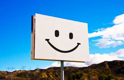 White roadside smiley billboard. White roadside billboard with smiley on the sky background Stock Images