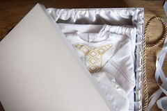 White robe embroidered with gold in a box Stock Photography