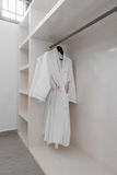 White robes with wooden hangers at dressroom. Royalty Free Stock Image