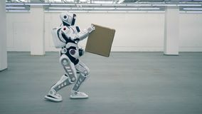 White robot carries a box, side view. One droid carries a big box in hands stock video