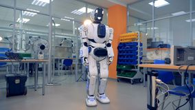 White robot looks around. A metal droid stands in a special room and looks around