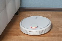 White Robot vacuum cleaner runs in corner near sofa on wood parquet floor. Modern smart cleaning technology housekeeping.  stock photos