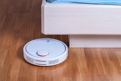 White Robot vacuum cleaner runs under bed in bedroom.  Royalty Free Stock Image